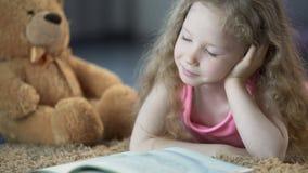 Söt liten flicka som absorberas i saga, läs- favorit- bok med intresse stock video
