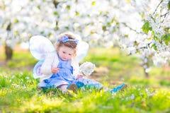 Söt litet barnflicka i felik dräkt i fruktäppleträdgård Arkivfoto