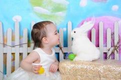 Söt litet barnflicka med kaninen på easter Royaltyfri Foto