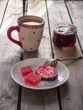 Söt lunch med tranbärmarshmallowen och marmelad, grönt te i ett stort keramiskt rånar och en exponeringsglaskrus med körsbärsrött royaltyfria foton
