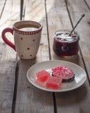 Söt lunch med tranbärmarshmallowen och marmelad, grönt te i ett stort keramiskt rånar och en exponeringsglaskrus med körsbärsrött royaltyfria bilder