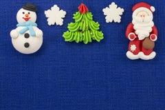 Söt mastix för julstatyetter på en blå bakgrund Arkivfoto