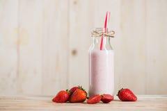 Söt milkshake med sugrör i flaska och nya jordgubbar Royaltyfria Foton