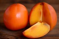 Söt ny persimon på en brun trätabell Skivar persimonfotoet Läckra vinterfrukter Fotografering för Bildbyråer