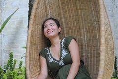 Söt och avkopplad asiatisk kinesisk kvinna på hennes 20-tal som bär den gröna sommarklänningen som ler lyckligt och skämtsamt sam Royaltyfri Foto