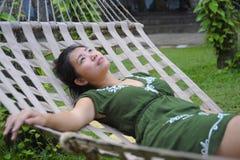 Söt och avkopplad asiatisk kinesisk kvinna på hennes 20-tal som bär liggande fundersamt eftertänksamt för grön sommarklänning och Royaltyfri Fotografi
