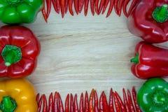 Söt peppar och chili på träbakgrund Arkivfoton