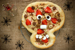 Söt pizza i form av den roliga skallen som behandlar ungar på Hallowee Arkivbild