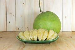 Söt pomelo som skalas på den gröna plattan Arkivbilder