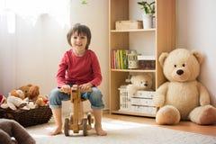 Söt pys, förskole- barn som hemma spelar med träH Royaltyfri Foto