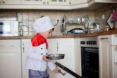 Söt pys som kläs som en kock som äter och klipper äpplen f arkivbilder