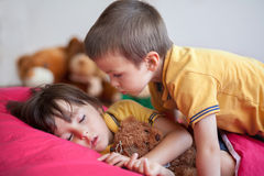 Söt pys som sover i eftermiddagen med hans nallebjörn, Arkivbild