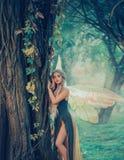 Söt skogängel, nymf med perfekt tjockt vitt hår i bild av den drömlika anden med fjärilsvingar attraktiv fe royaltyfri fotografi
