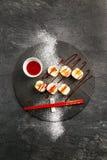 Söt sushi med rött jordgubbedriftstopp på en svart platta Royaltyfria Bilder