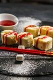 Söt sushi med rött jordgubbedriftstopp på en svart platta Arkivfoton