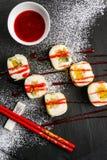 Söt sushi med rött jordgubbedriftstopp på en svart platta Arkivbild