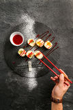 Söt sushi med rött jordgubbedriftstopp på en svart platta Royaltyfri Fotografi