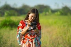 Söt ung asiatisk kines- eller koreankvinna på hennes 20-tal som kontrollerar bilden i fotokamera i härligt naturlandskap i ferier Arkivbilder