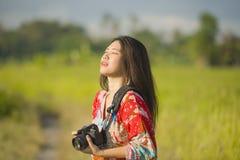 Söt ung asiatisk kines- eller koreankvinna på hennes 20-tal som tar bilden med att le för fotokamera som är lyckligt i härligt na Royaltyfria Bilder
