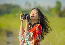 Söt ung asiatisk kines- eller koreankvinna på hennes 20-tal som tar bilden med att le för fotokamera som är lyckligt i härligt na Arkivfoto