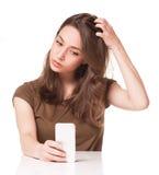 Söt ung brunett genom att använda mobiltelefonen Arkivbild