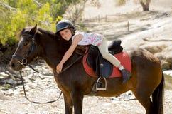 Söt ung flicka som kramar ponnyhästen som ler den lyckliga bärande säkerhetsjockeyhjälmen i sommarferie Royaltyfria Foton