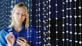 Söt ung kvinna som skriver ett meddelande på en smartphone i en nattklubb Henne ` s i en blå skjorta med härliga blåa ögon stock video