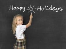 Söt yngre skolflicka med anseendet för blont hår som är lyckligt och ler handstil med lyckliga ferier för krita Fotografering för Bildbyråer