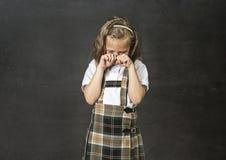Söt yngre skolflicka med att gråta för blont hår som är ledset framme av skolaklassrumsvart tavla Royaltyfria Bilder