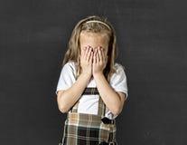 Söt yngre skolflicka med gråt för blont hår som är ledsen och som är blyg framme av svart tavla för skolagrupp Arkivfoto