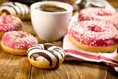 Söta amerikanska donuts på tabellen och koppen kaffe arkivbild