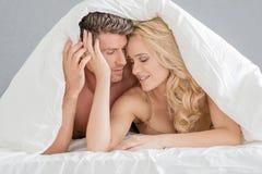 Söta barnpar på sängmodefors Arkivfoton