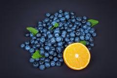 Söta blåbär med mogen halva av apelsinen och gräsplanmintkaramellen Hela blåbär med halva av apelsinen och mintkaramellen på en m Arkivfoto