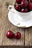 Söta Cherry i en vit kopp Arkivbild