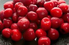 Söta Cherry på svart maträtt Arkivfoton