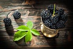 Söta dewberries i hink på tappningträbräde arkivfoton