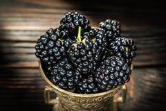 Söta dewberries i metall bowlar på tappningträbräde fotografering för bildbyråer