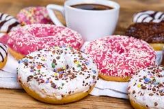 Söta donuts och kopp kaffe på tabellen, den amerikanska munken och koppen av coffe arkivbild