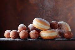 Söta donuts som pudras med socker på en brun bakgrund royaltyfria bilder