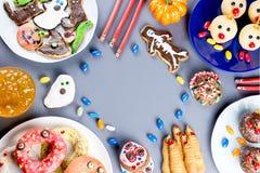 Söta fester för allhelgonaafton, partimatbegrepp Läskiga kakor, gigantiska kex och frukter på grå bakgrund arkivfoton