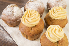 Söta frodiga muffin med kräm- och som dammar av med pudrat socker Arkivfoton