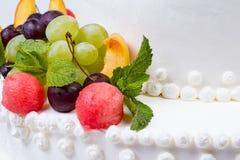Söta frukter på den vita bröllopstårtan Arkivbild