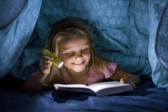 Söta härliga och nätta små blonda för sängräkningar för flicka 6 till 8 år gammal under-läsebok i mörkret på natten med facklalju Fotografering för Bildbyråer