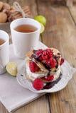 Söta hem- punkcakes med vitkräm och nya bär för rött hallon Två exponeringsglas av te för frukost på en träbakgrund royaltyfri fotografi