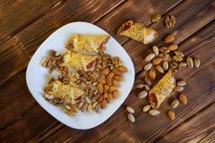 Söta hemlagade kakor med driftstopp, en blandning av pistascher, mandlar och valnötter ligger i en vit platta på en trätabell gjo royaltyfria bilder