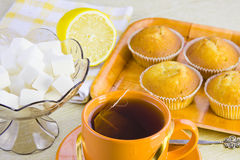 Söta inhemska tårtor, tea, citron och vase med socker arkivfoton