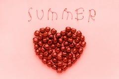 Söta körsbär för rött bär i form av hjärta- och textsommar av moderiktig korallskugga, färg av den årsmallen 2019 för vykort elle arkivfoto