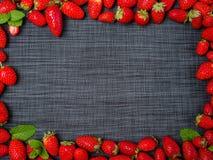 Söta nya jordgubbar på en grå bakgrund olivgrön för olja för kök för kockbegreppsmat ny över hällande restaurangsallad Arkivfoton