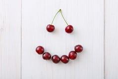 Söta nya körsbär ler på vit wood bakgrund Royaltyfria Bilder