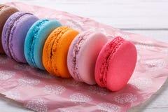 Söta och färgglade franska makron eller macaron på rosa färger skyler över brister över vit träbakgrund royaltyfri foto